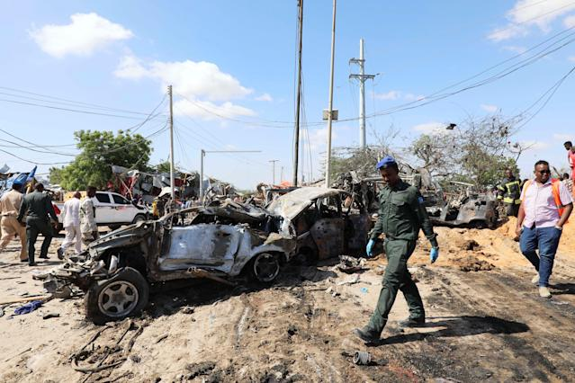 A Somali police officer walks past a wreckage at the scene of a car bomb (Picture: Reuters)