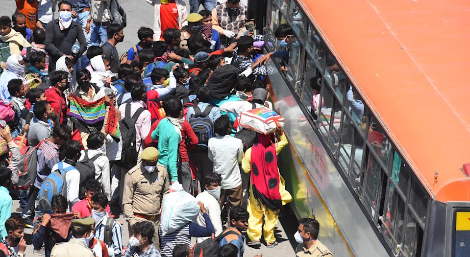 NEW DELHI, INDIA - MARCH 28: A wave of migrant workers try to board a bus bound to their native state at Ghazipur, near the Delhi - UP border on Day 4 of the 21 day nationwide lockdown -- to check the spread of coronavirus, on March 28, 2020 in New Delhi, India. (Photo by Raj K Raj/Hindustan Times via Getty Images)