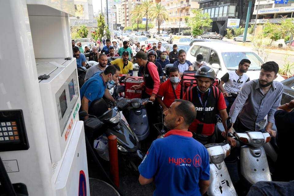 Motorists crowd a petrol station to get fuel as supplies are rationed (EPA)
