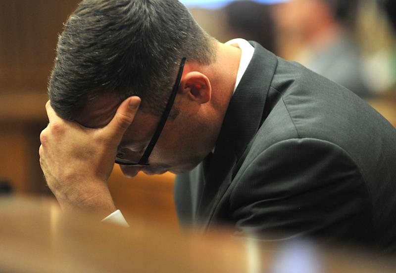 Oscar Pistorius holds his head in his hands as he listens to evidence being given in court in Pretoria, South Africa, Monday March 24, 2014. Pistorius is on trial for the shooting death of his girlfriend Steenkamp on Valentine's Day 2013. (AP Photo/Ihsaan Haffejee, Pool)