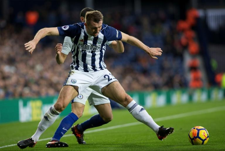 Chelsea's Davide Zappacosta (rear) fights for the ball with West Bromwich Albion's Gareth McAuley during their English Premier League match, at The Hawthorns stadium in West Bromwich, on November 18, 2017