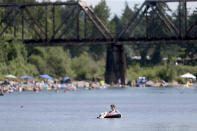People gather at the Sandy River Delta, in Ore., to cool off during the start of what should be a record-setting heat wave on June 25, 2021. The Pacific Northwest sweltered Friday as a historic heat wave hit Washington and Oregon, with temperatures in many areas expected to top out 25 to 30 degrees above normal in the coming days. (Dave Killen/The Oregonian via AP)