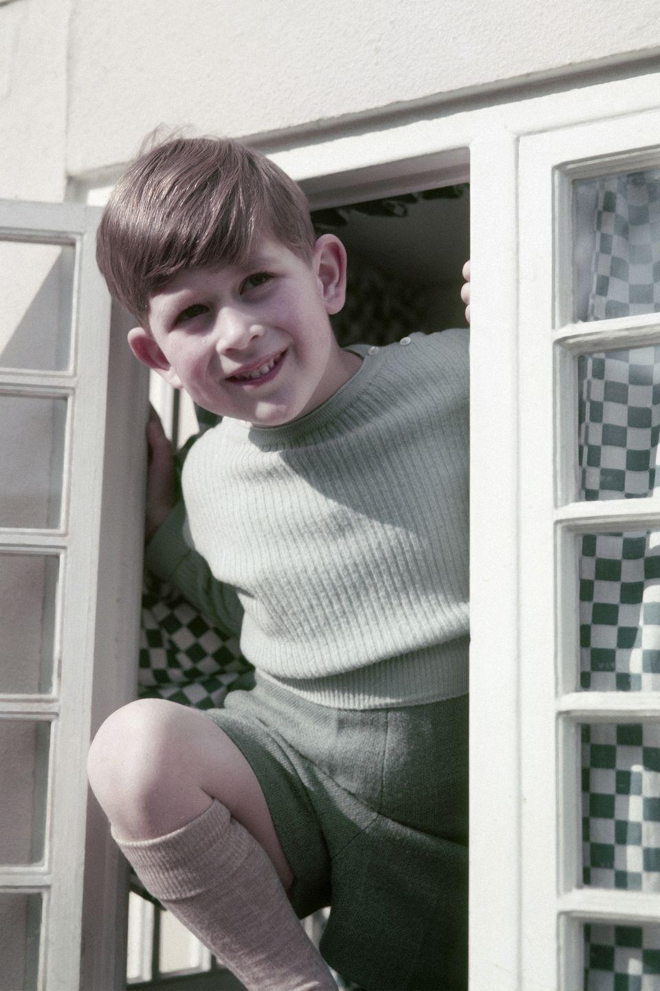 <p>Prince Charles smiles cheekily as he peeks out the window of a cottage in Windsor.</p>