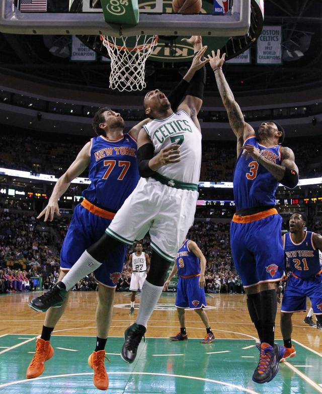 Boston Celtics' Jared Sullinger (7) battles New York Knicks' Andrea Bargnani (77) and Kenyon Martin (3) for a rebound in the first quarter of an NBA basketball game in Boston, Friday, Dec. 13, 2013. (AP Photo/Michael Dwyer)