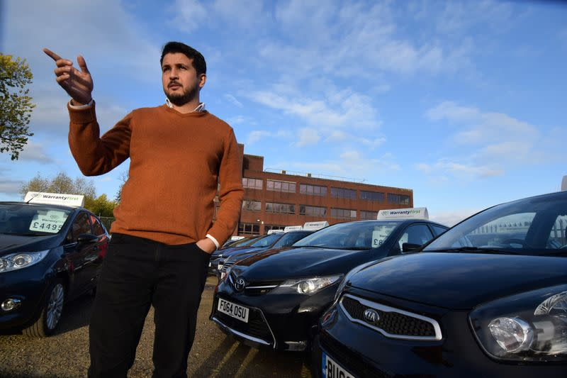 Ameen Sultani speaks as he shows some of the older, cheaper vehicles that have been popular with customers eager to avoid public transport during the coronavirus disease (COVID-19) pandemic, in Hayes