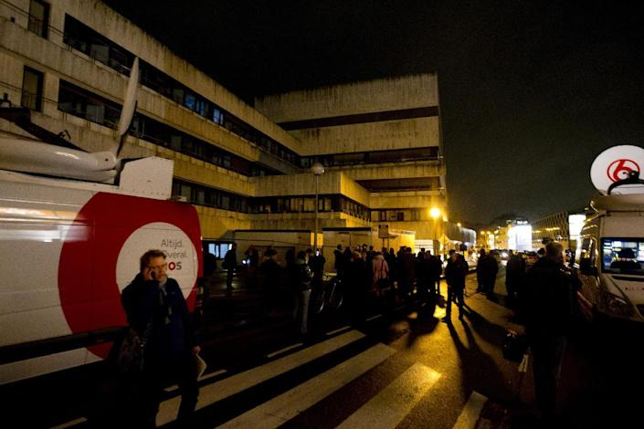 News vans and people gather outside the offices of Dutch national broadcaster NOS in Hilversum, the Netherlands, on January 29, 2015, after a man was overpowered after entering the building and demanding airtime (AFP Photo/Robin Van Lonkhuijsen)