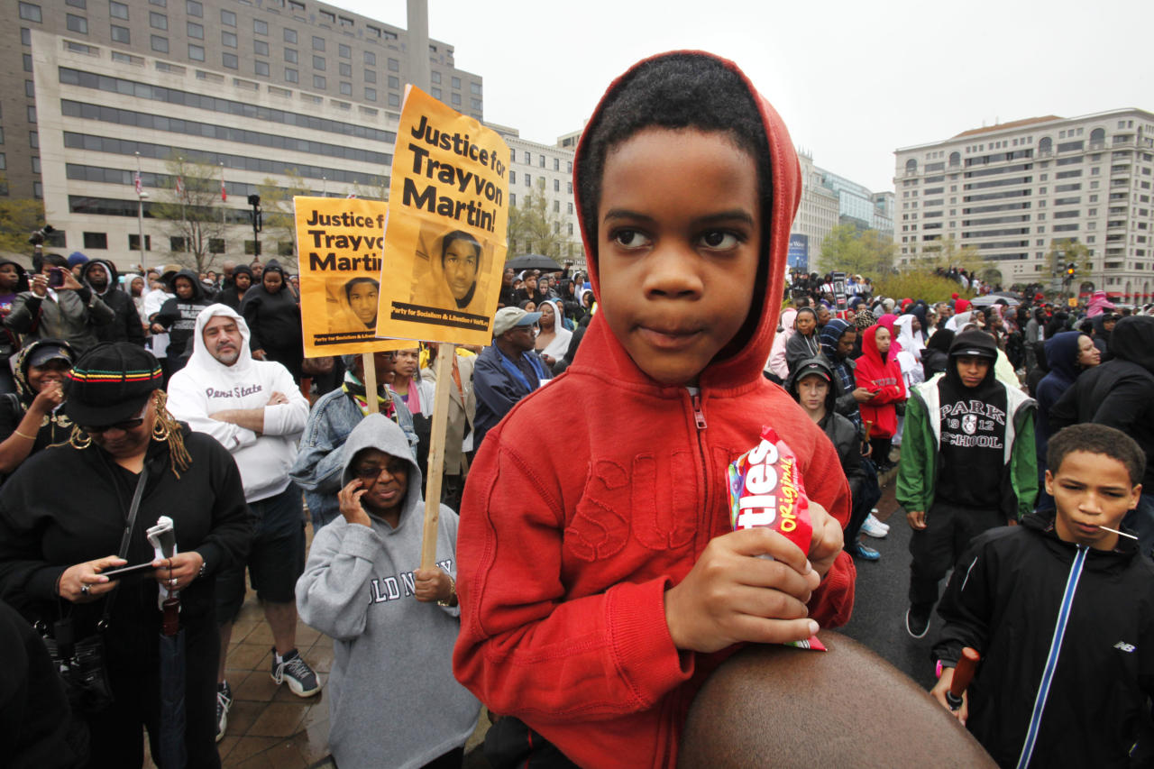 Isaiah Henry-Simpson, 7, of Arlington, Va., eats Skittles candy while attending a rally with his parents in support of Trayvon Martin at Freedom Plaza in Washington, on Saturday, March 24, 2012. Many people in attendance brought candy, ice tea, and wore hooded sweatshirts, or hoodies, in support of the unarmed young black teen, who was fatally shot by a volunteer neighborhood watchman. (AP Photo/Jacquelyn Martin)(AP Photo/Jacquelyn Martin)