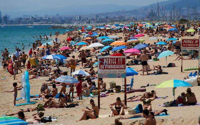 People enjoy sunny weather at the beach, Barcelona, Spain - Shutterstock