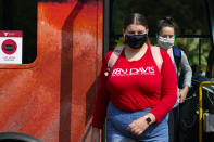 FILE - Masked students disembark from a bus on the campus of Ball State University in Muncie, Ind., Thursday, Sept. 10, 2020. Colleges across the country are struggling to salvage the fall semester as campus coronavirus cases skyrocket and tensions with local health leaders flare. Schools have locked down dorms, imposed mask mandates, barred student fans from football games and toggled between online and in-person classes. (AP Photo/Michael Conroy)