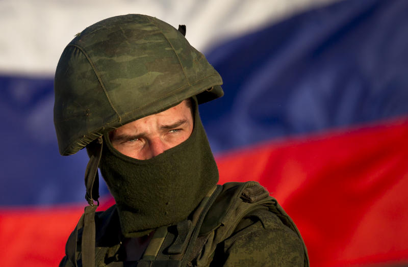 A pro-Russian soldier is back dropped by Russia's flag while manning a machine-gun outside an Ukrainian military base in Perevalne, Ukraine, Saturday, March 15, 2014. Tensions are high in the Black Sea peninsula of Crimea, where a referendum is to be held Sunday on whether to split off from Ukraine and seek annexation by Russia.(AP Photo/Vadim Ghirda)