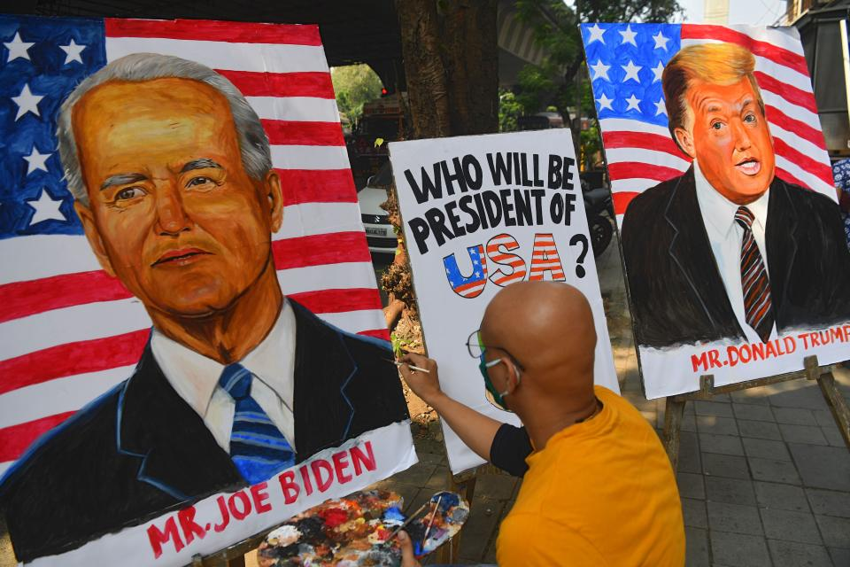 An Indian art school teacher paints an image of Democratic Presidential Candidate and former US Vice President Joe Biden next to the image of US President Donald Trump ahead of the upcoming US presidential elections, outside an art school in Mumbai on October 29, 2020. (Photo by INDRANIL MUKHERJEE / AFP) (Photo by INDRANIL MUKHERJEE/AFP via Getty Images)