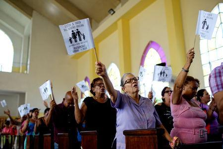"""FILE PHOTO: Worshippers wave paper flags that read in Spanish """"I am in favour of the original design. The family as God created it. Wedding between man and woman"""", during a service at a Methodist Church in Havana, Cuba, October 4, 2018. REUTERS/Alexandre Meneghini"""