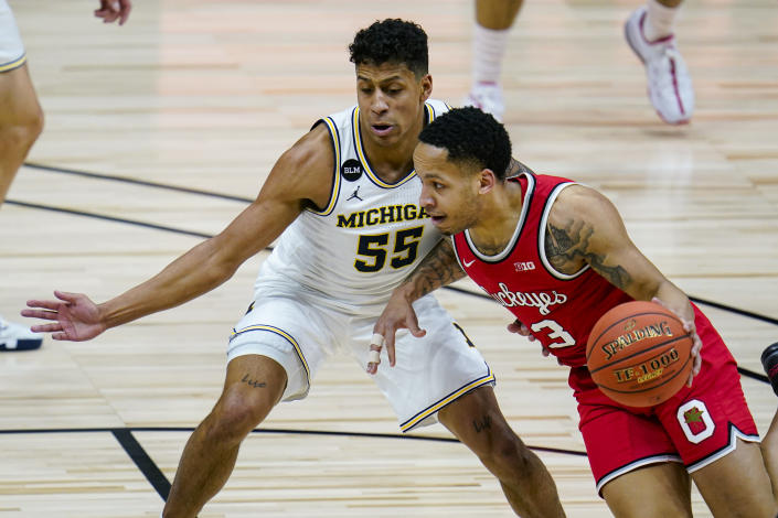 Ohio State guard CJ Walker (13) drives on Michigan guard Eli Brooks (55) in the first half of an NCAA college basketball game at the Big Ten Conference tournament in Indianapolis, Saturday, March 13, 2021. (AP Photo/Michael Conroy)