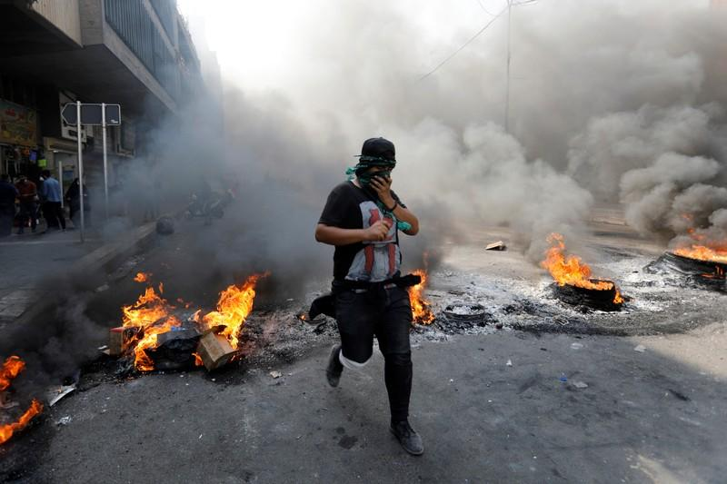 An Iraqi demonstrator jump above burning tires as he blocks the road during ongoing anti-government protests, in Baghdad