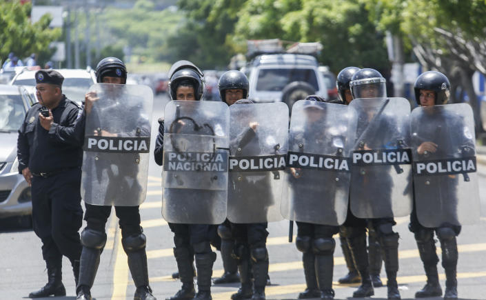 Police stand outside the Central American University (UCA), where they cannot legally enter, as they watch students protest inside the campus, demanding the release of all political prisoners on the last day of a 90-day period for releasing such prisoners, as agreed during negotiations between the government and opposition, in Managua, Nicaragua, Tuesday, June 18, 2019. Nicaragua's government said Tuesday that it has released all prisoners detained in relation to 2018 anti-government protests, though the opposition maintains that more than 80 people it considers political prisoners are still in custody. (AP Photo/Alfredo Zuniga)