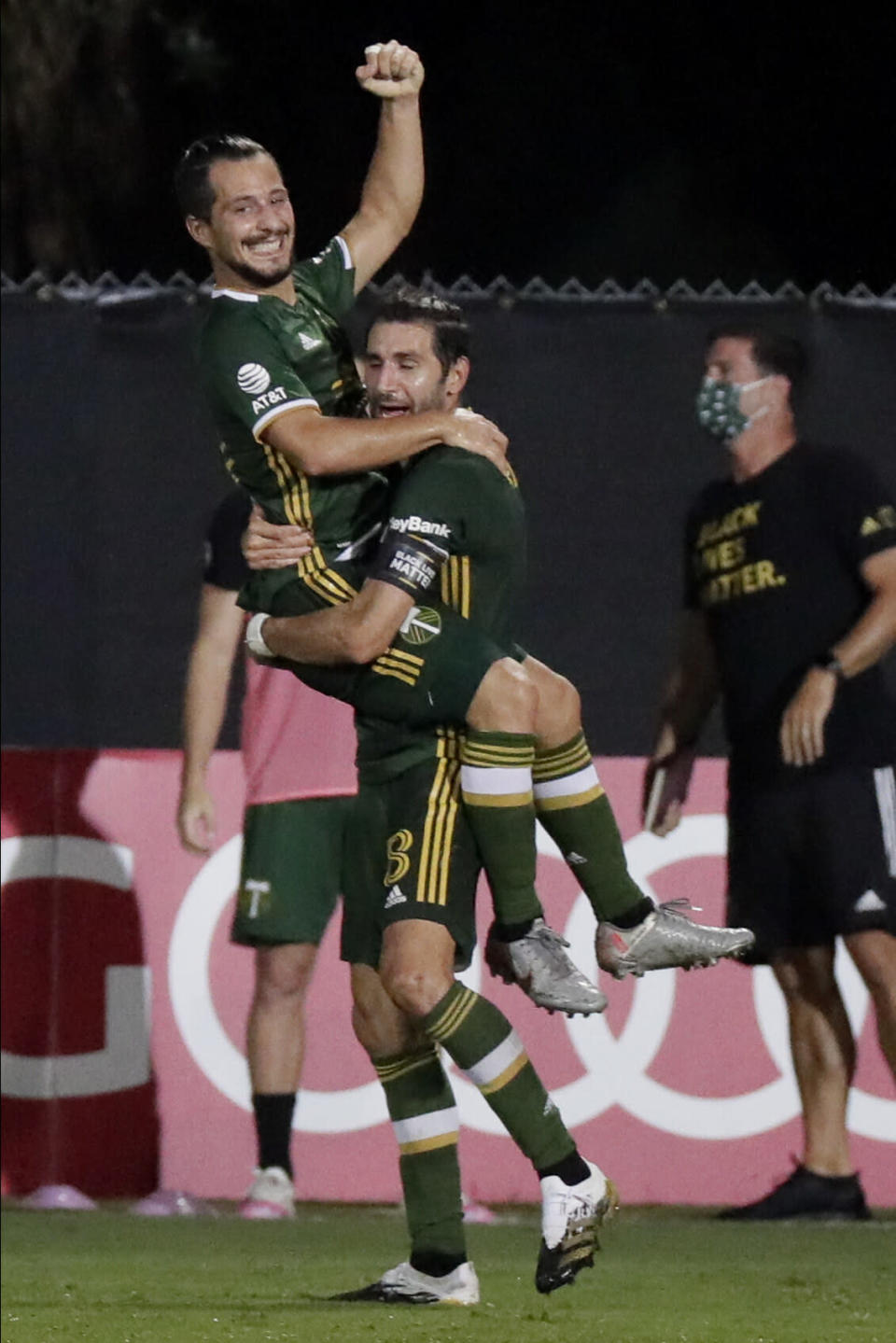 Portland Timbers midfielder Sebastian Blanco, top, celebrates his goal with Diego Valeri against the Philadelphia Union during the second half of an MLS soccer match, Wednesday, Aug. 5, 2020, in Kissimmee, Fla. (AP Photo/John Raoux)