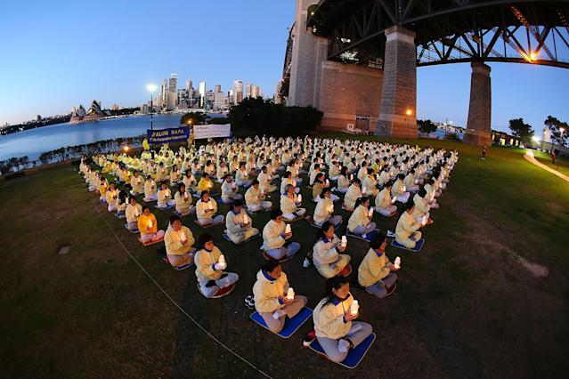 SYDNEY, AUSTRALIA - JULY 21: Falun Gong Practitioners hold candles for a vigil to mark the 14th anniversary of the beginning of the persecution of Falun Gong in China on July 21, 2013 in Sydney, Australia. In July of 1999, the communist Chinese government outlawed the spiritual practise of Falun Gong, declaring it illegal and forbidding citizens to practise. Followers believe thousands of practitioners have been killed, imprisoned or put in labour camps in China since 1999. (Photo by Brendon Thorne/Getty Images)