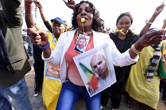 A woman dances as she wears pictures of Karim Wade, during a meeting of the opposition on February 4, 2015 in Dakar (AFP Photo/Seyllou Diallo)