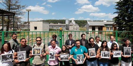 FILE PHOTO: Participants of the European Meeting of Antiracist Leaders hold pictures in front of a pig farm, situated at the site of a former Roma concentration camp, to commemorate victims of the Holocaust during World War Two in the village of Lety June 13, 2014. REUTERS/David W Cerny/File Photo
