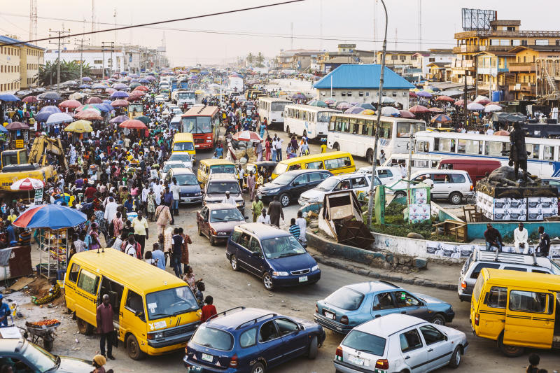 Traffic and street market in Ikorodu district just before sunset.