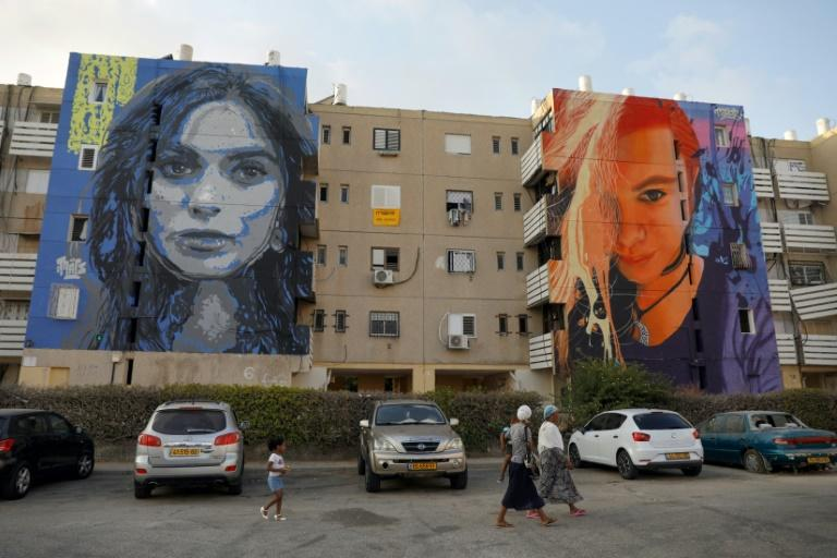 A family walks past murals in an impoverished neighbourhood in the Israeli city of Ashkelon (AFP Photo/MENAHEM KAHANA)