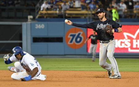 Jun 9, 2018; Los Angeles, CA, USA; Atlanta Braves shortstop Dansby Swanson (right) turns a double play over Los Angeles Dodgers right fielder Yasiel Puig (66) in the 9th inning at Dodger Stadium. Mandatory Credit: Richard Mackson-USA TODAY Sports