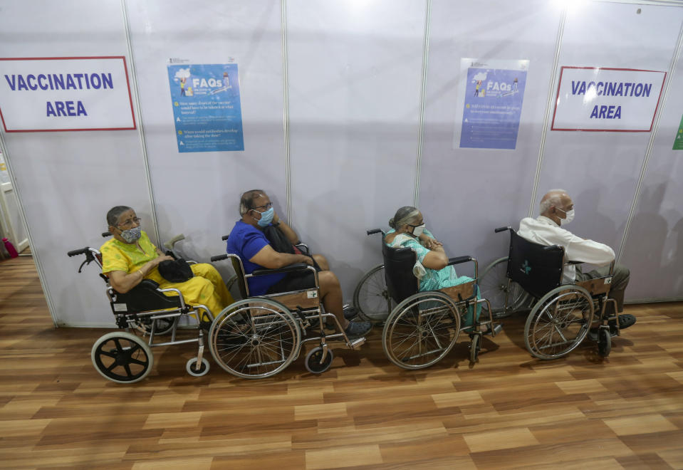 Elderly Indians on wheel chairs wait in a queue to receive COVID-19 vaccine in Mumbai, India, Monday, March 8, 2021. (AP Photo/Rafiq Maqbool)