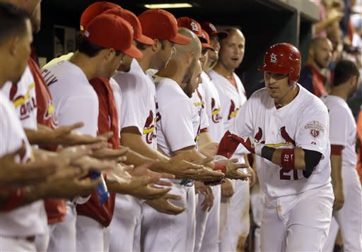 St. Louis Cardinals' Allen Craig, right, is congratulated by teammates in the dugout after hitting a solo home run during the eighth inning of a baseball game Monday, July 2, 2012, in St. Louis. The home run was Craig's second of the game. (AP Photo/Jeff Roberson)