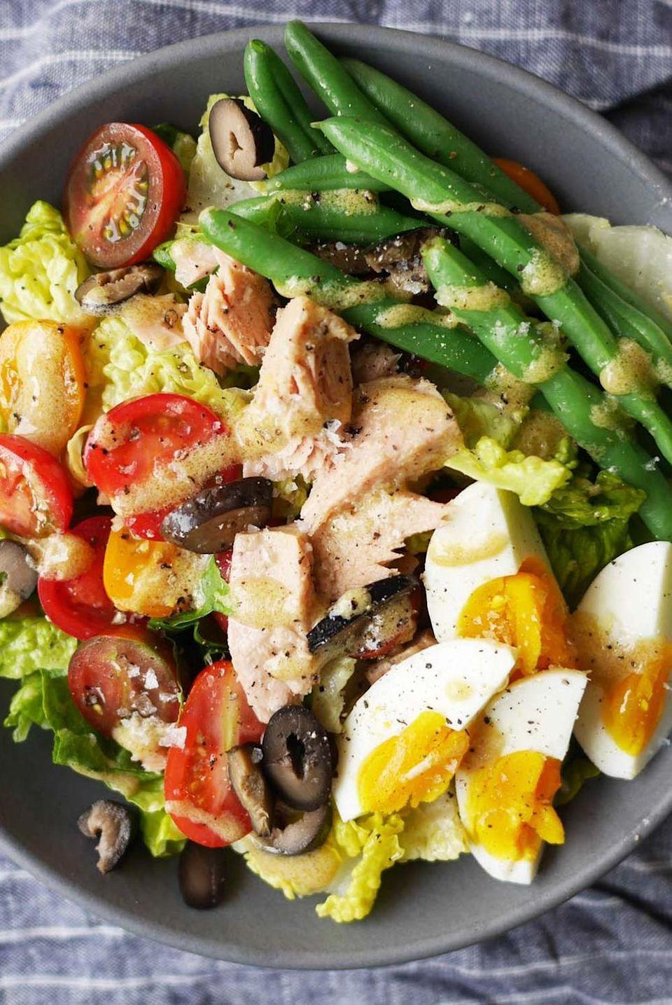 """<p>An easy twist on a classic dish, this chopped salad features hard-boiled eggs, tomatoes, tuna, and olives for a filling dish. </p><p><strong><em>Get the recipe at <a href=""""https://www.delish.com/cooking/recipe-ideas/recipes/a42758/best-nicoise-salad-recipe/"""" rel=""""nofollow noopener"""" target=""""_blank"""" data-ylk=""""slk:Delish"""" class=""""link rapid-noclick-resp"""">Delish</a>.</em></strong></p>"""