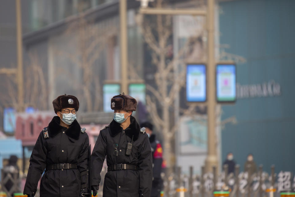 Security officers wearing face masks to prevent the spread of the coronavirus walk on patrol at a pedestrian shopping street in Beijing, Saturday, Jan. 23, 2021. (AP Photo/Mark Schiefelbein)