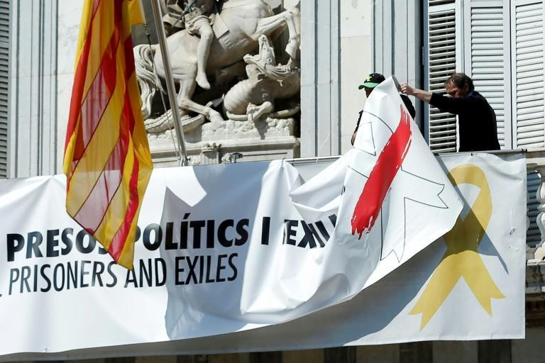 Barcelona City Hall officials taking down a banner bearing that reads lFreedom for political prisoners and exiles' last March