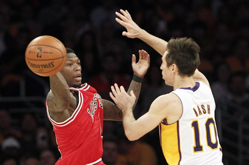 Chicago Bulls guard Nate Robinson (2) passes as Los Angeles Lakers guard Steve Nash (10) defends in the first half of an NBA basketball game in Los Angeles Sunday, March 10, 2013. (AP Photo/Reed Saxon)