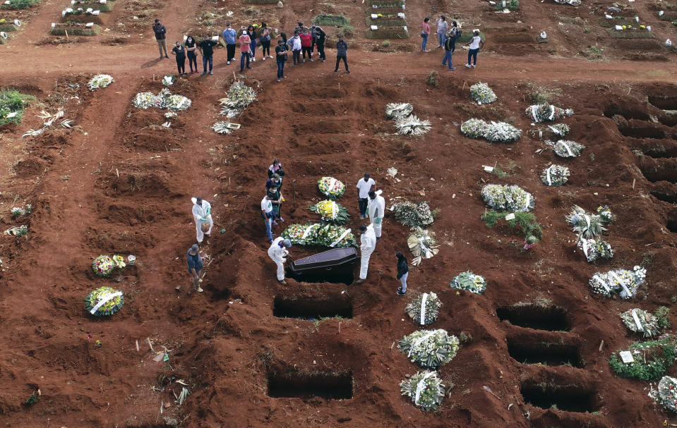FILE - In this April 7, 2021, file photo, cemetery workers wearing protective gear lower the coffin of a person who died from complications related to COVID-19 into a gravesite at the Vila Formosa cemetery in Sao Paulo, Brazil. Nations around the world set new records Thursday, April 8, for COVID-19 deaths and new coronavirus infections, and the disease surged even in some countries that have kept the virus in check. Brazil became just the third country, after the U.S. and Peru, to report a 24-hour tally of COVID-19 deaths exceeding 4,000. (AP Photo/Andre Penner, File)