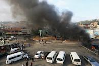 Demonstrators stand near burning tires blocking streets during a protest targeting the government over an economic crisis, in Nabatiyeh