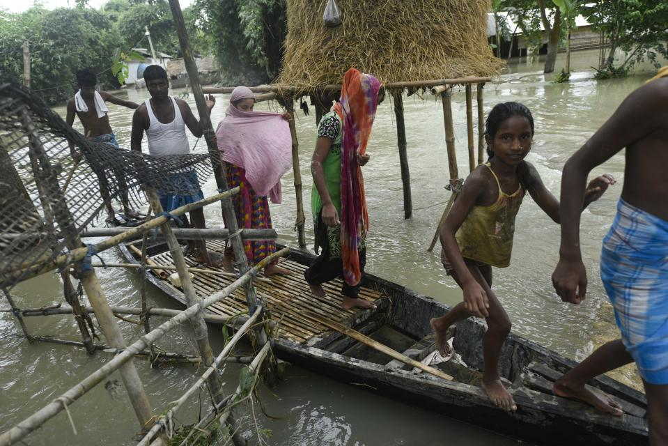 Villagers uses a boat to move across a flooded area in a flood effected village in Morigaon district of Assam in India on Friday, 17 July 2020. (Photo by David Talukdar/NurPhoto via Getty Images)