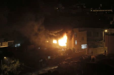 Flames and smoke are seen after a blast in the top floor of the family home of an alleged abductor in the West Bank City of Hebron