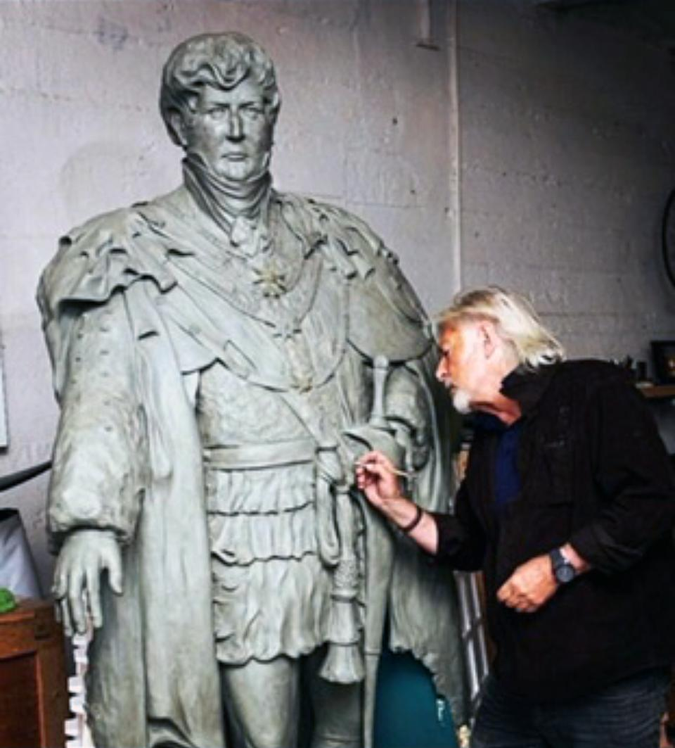 Dominic Grant recently at work on a statue of King George IV (PA)