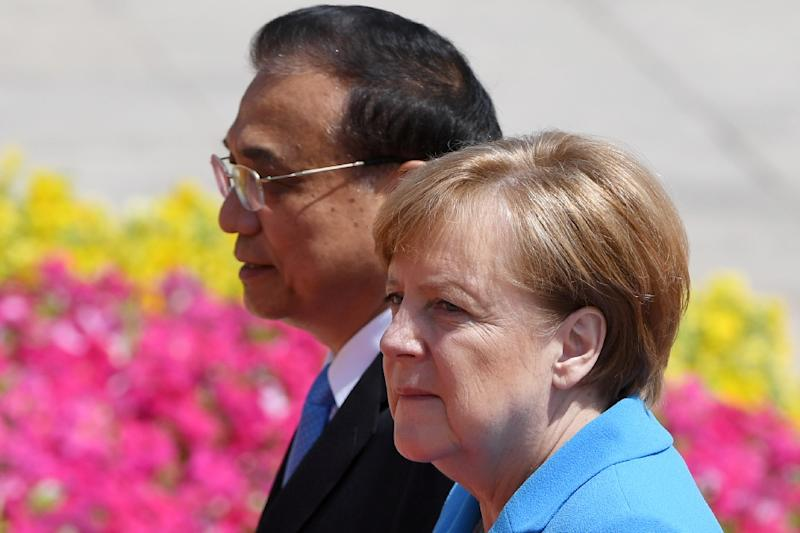 German Chancellor Angela Merkel and Chinese Premier Li Keqiang defended the Iran nuclear deal on Thursday, with Li hinting that terminating the pact would complicate negotiations with North Korea (AFP Photo/GREG BAKER)