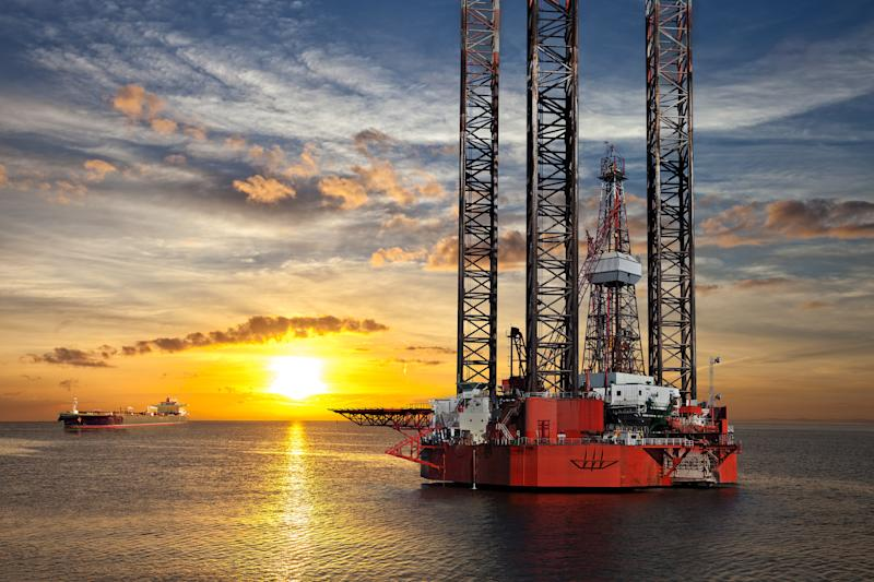An offshore drilling rig at sunset with a ship in the background.