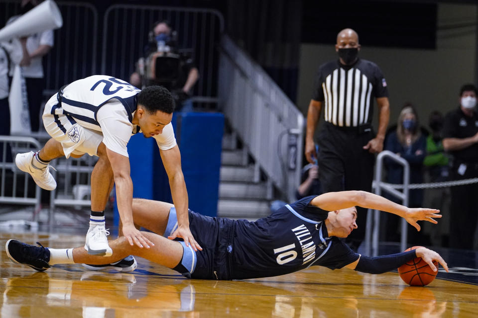 Villanova forward Cole Swider (10) attempts to save the ball under Butler guard Jair Bolden (52) in the second half of an NCAA college basketball game in Indianapolis, Sunday, Feb. 28, 2021. (AP Photo/Michael Conroy)