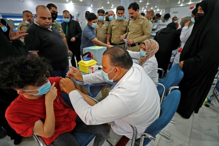 Soliders watch on as an Iraqi medic administers a dose of the Pfizer/BioNTech Covid-19 vaccine to a man in the capital Baghdad, on July 27, 2021