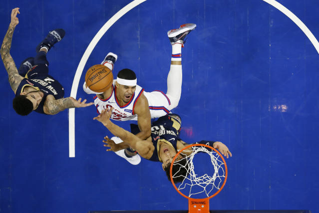 Philadelphia 76ers' Tobias Harris, center, goes up to shoot against New Orleans Pelicans' Jaxson Hayes, right, and Lonzo Ball during the first half of an NBA basketball game, Friday, Dec. 13, 2019, in Philadelphia. (AP Photo/Matt Slocum)