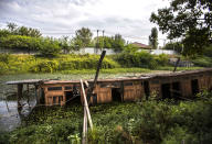 A broken house boat lies surrounded by weeds in the Dal Lake in Srinagar, Indian controlled Kashmir, Saturday, Aug. 28, 2021. Weeds, silt and untreated sewage are increasingly choking the sprawling scenic lake, which dominates the city and draws tens of thousands of tourists each year. (AP Photo/Mukhtar Khan)