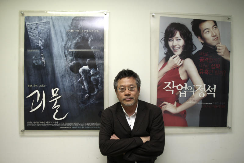 In this July 17, 2012 photo, Choi Yong-bae, Chungeoraham Film CEO and Producer, poses with posters produced by his company during an interview with the Associated Press at his office in Seoul, South Korea. After being turned down by many investors over the last four years, Choi said it feels strange and exciting that his revenge film about a notorious South Korean president blamed for the massacre of democracy protesters is finally coming to life through online donations. (AP Photo/Ahn Young-joon)