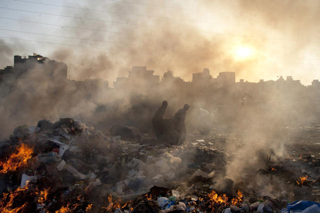 <p>Afghan refugees collect recyclable items from a a heap of garbage to earn their livings, Jan. 28, 2015. (AP Photo/Shakil Adil) </p>