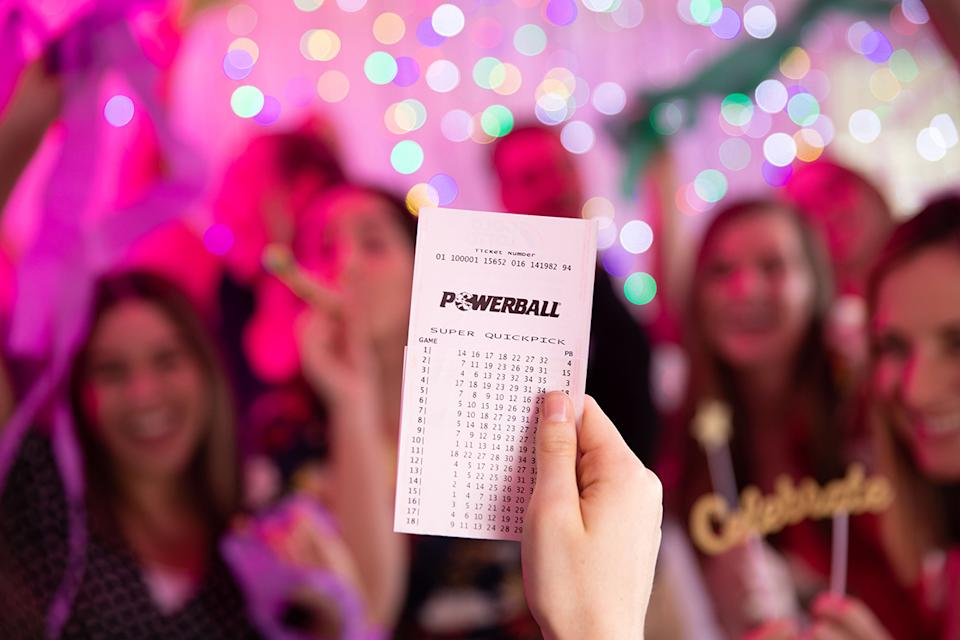 Powerball ticket held in front of celebrating crowd.