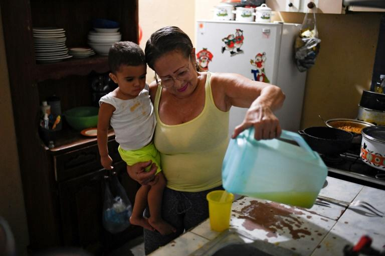 Venezuelan Minu Vasquez, 64, serves a glass of juice to her grandson, whom she takes care after his parents emigrated, at her house in the San Agustin neighborhood in Caracas