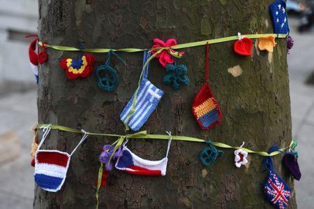 Knitted European flags hang from a ribbon tied around a tree during a protest in favour of amendments to the Brexit Bill outside the Houses of Parliament, in London, Britain, March 13, 2017. REUTERS/Neil Hall