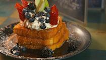 """<p>If Cap'n Crunch and French toast had a baby, this would be it. Chefs coat slices of <a rel=""""nofollow noopener"""" href=""""https://www.delish.com/restaurants/videos/a53942/blue-moon-cafe-capn-crunch-toast-video/"""" target=""""_blank"""" data-ylk=""""slk:Texas Toast in the cereal"""" class=""""link rapid-noclick-resp"""">Texas Toast in the cereal</a> before frying them and topping a three-piece stack with all the fruit. There are three types of berries, apples, and bananas.</p>"""