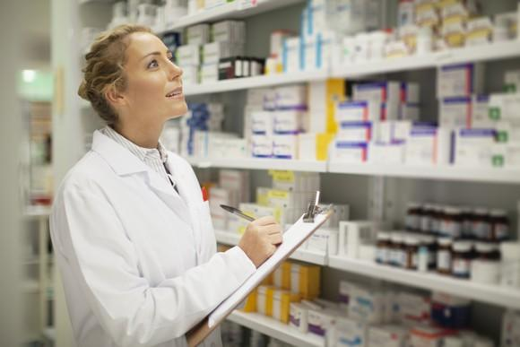 A female pharmacist writing on a clipboard while looking at medicines on shelves.